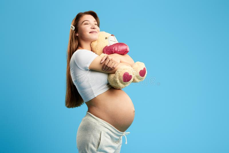 Excited smiling woman hugging, embracing teddy bare. Close up portrait. isolated blue background. studio shot. copy space. love. expectation . happiness stock photos