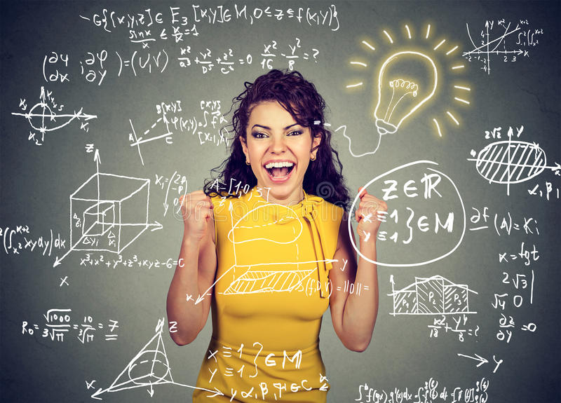 Excited student with idea light bulb and maths and science formulas on blackboard stock photography