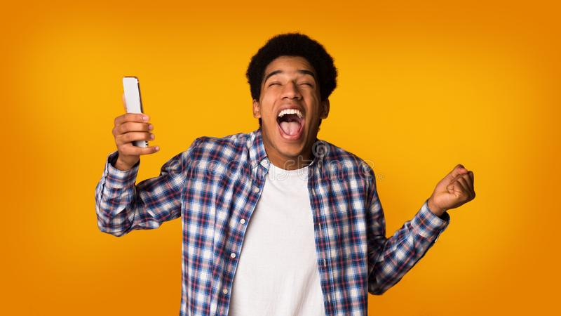 Excited student with phone celebrating victory, studio background stock photography
