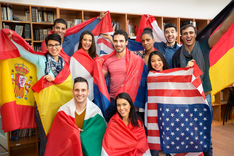 Excited students presenting their countries with flags stock images