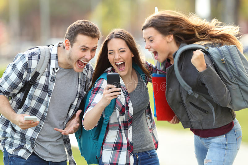 Excited students receiving good news on phone. Front view of three excited students receiving good news on line in a mobile phone in an university campus or stock photo