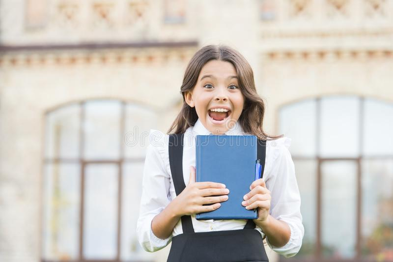 Excited about studying. School education concept. Cute smiling child hold book. Little girl school student. Knowledge stock image