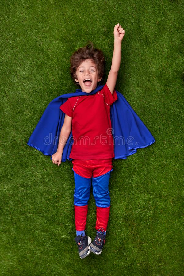 Excited superhero reaching dream on lawn. From above amazed little boy in superhero costume flying to achieve goal over green grass royalty free stock photography