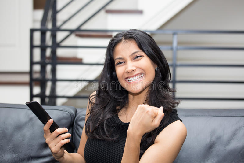 Excited surfing TV. Closeup portrait, young woman in black shirt, sitting on leather couch fists pumped, watching TV, holding remote, thrilled at what she sees stock photo