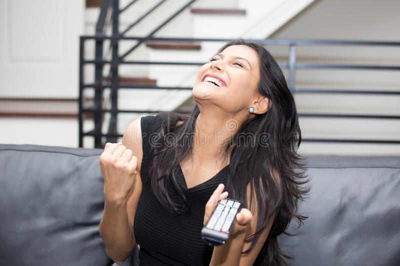 Excited surfing TV. Closeup portrait, young woman in black shirt, sitting on leather couch fists pumped, watching TV, holding remote, thrilled at what she sees royalty free stock image