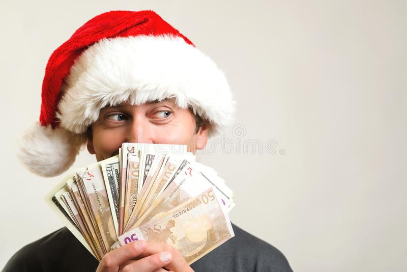 Excited surprised man wearing Christmas hat holding money. Christmas concept. Happy man holding up a lot of cash and looking aside royalty free stock images