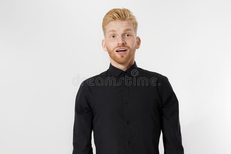 Excited surprised shock young shouting man  on gray background. Happy Redhead guy with red beard in black stylish shirt. stock photo