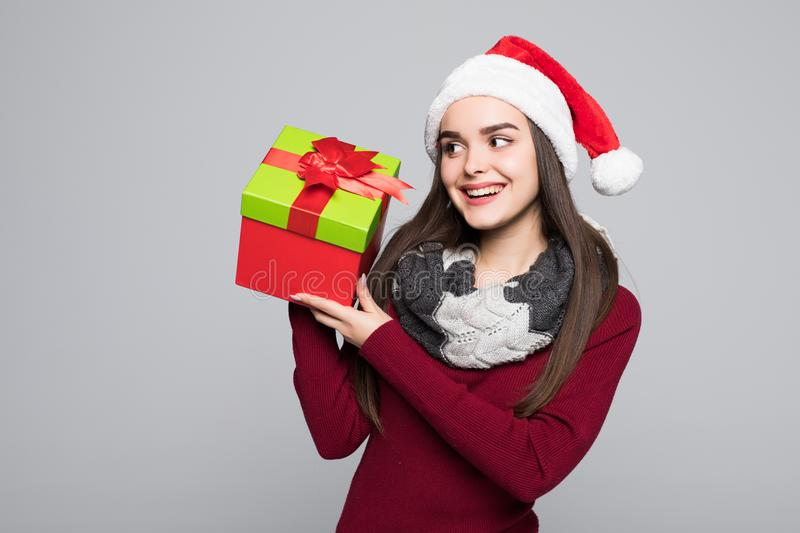 Excited surprised woman in red santa claus outfit holding stack presents isolated on the gray background stock photo
