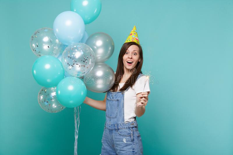 Excited surprised young woman in birthday hat holding burning sparkler, celebrating with colorful air balloons isolated. On blue turquoise background. Birthday stock photos