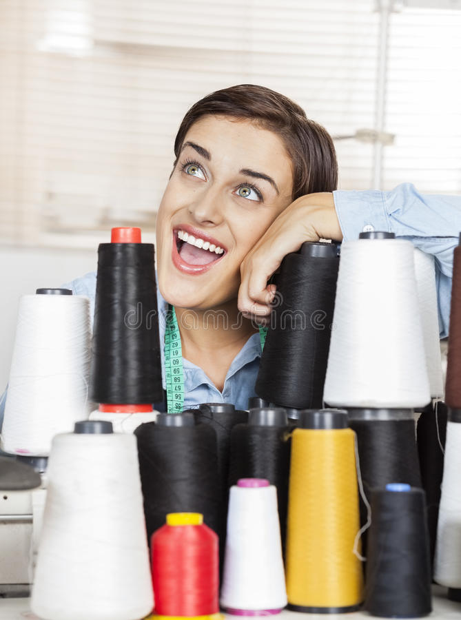 Excited Tailor Leaning On Stacked Thread Spools royalty free stock image