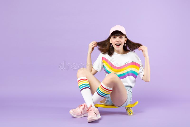 Excited teen girl in vivid clothes sitting on yellow skateboard, keeping mouth open isolated on violet pastel wall stock photo