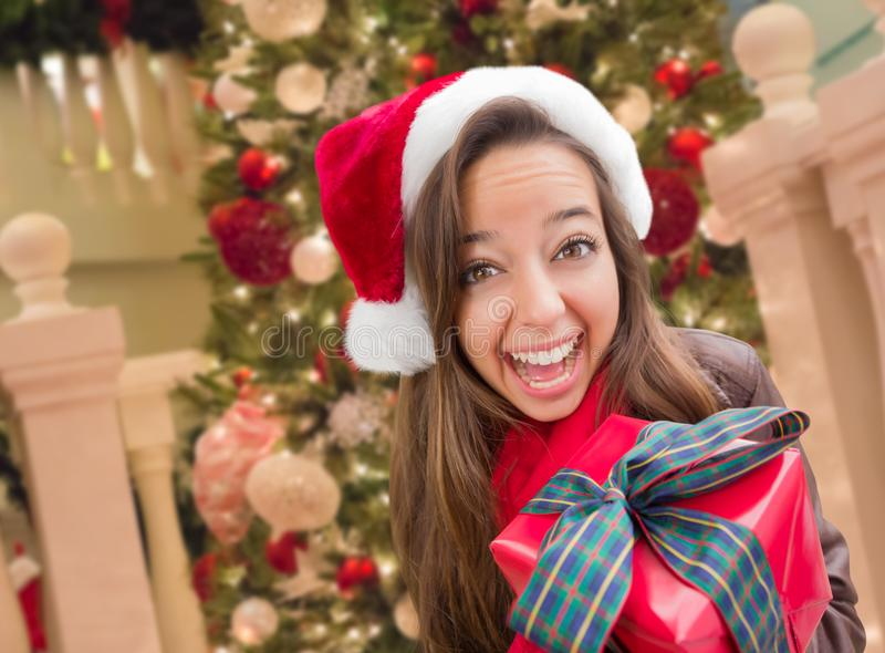 Excited Teen Girl Wearing A Christmas Santa Hat with Bow Wrapped Gift In Fron. Girl Wearing A Christmas Santa Hat with Bow Wrapped Gift In Front of Decorated stock images