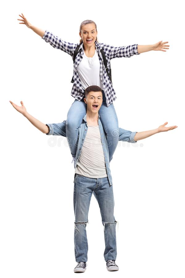 Excited teenage boy carrying a girl on his shoulders stock photo