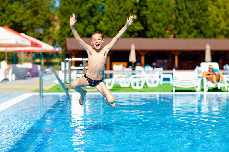Excited teenage boy jumping in the pool royalty free stock image