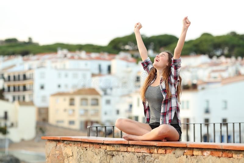 Excited teenage girl celebrating new day on a ledge stock photography