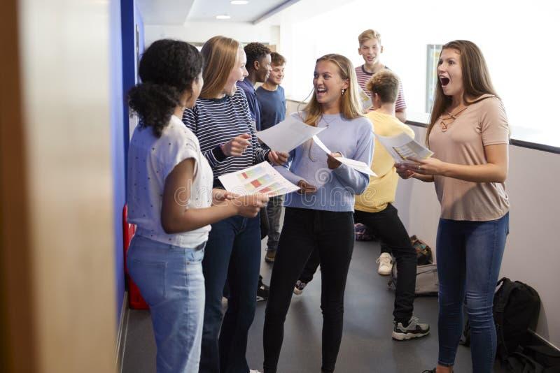 Excited Teenage High School Students Celebrating Exam Results In School Corridor stock image