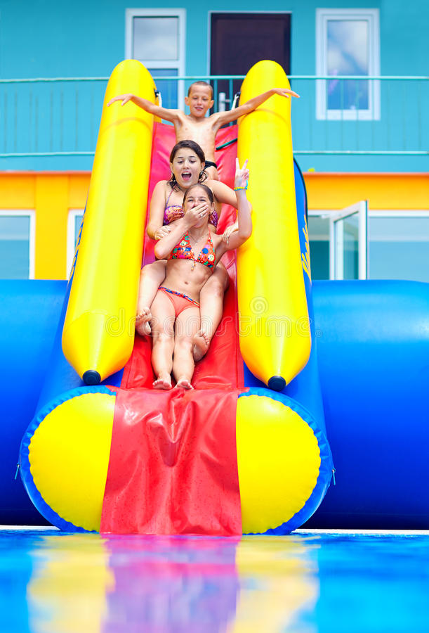 Excited teenage kids down on water slide. Excited teenage kids down on the water slide royalty free stock photography