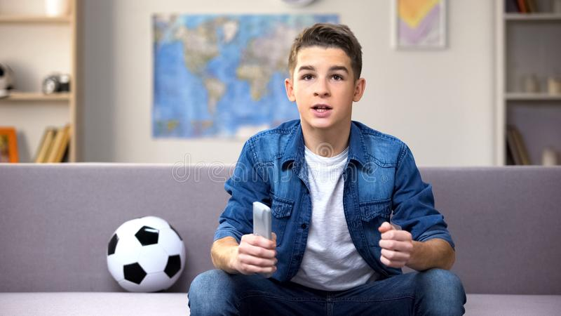 Excited teenage student watching football match on TV cheering for national team. Stock photo royalty free stock photo