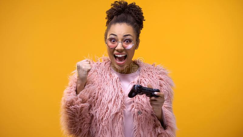 Excited teenager sincerely rejoicing victory in video game, playing controller. Stock photo royalty free stock photography