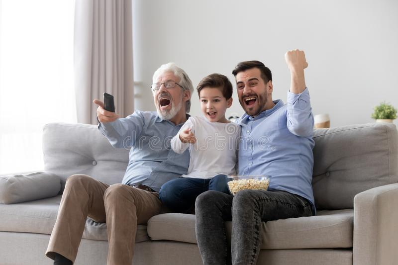 Excited three generation men family watch tv sport game royalty free stock photography