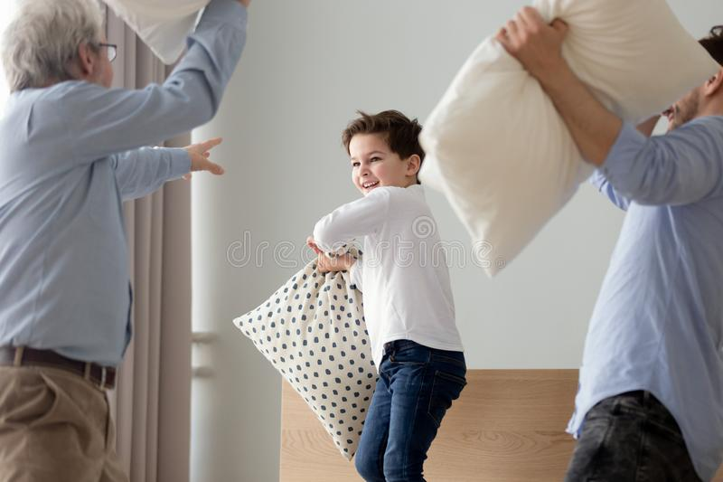 Excited three generations of men engaged in pillow fight. Playful little boy have fun in bedroom engaged in pillow fight with young father and grandfather, happy royalty free stock photos