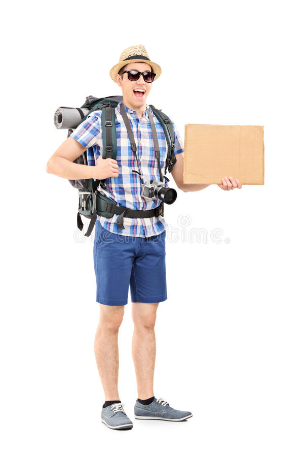 Excited tourist holding a blank cardboard sign. Full length portrait of an excited tourist holding a blank cardboard sign isolated on white background royalty free stock photo