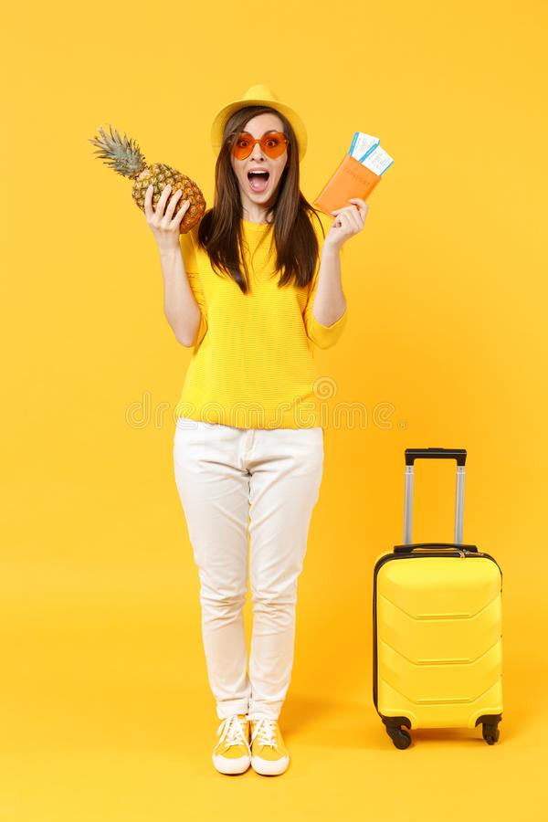 Excited traveler tourist woman in hat holding passport tickets, fresh pineapple fruit isolated on yellow orange. Background. Passenger traveling abroad on stock image