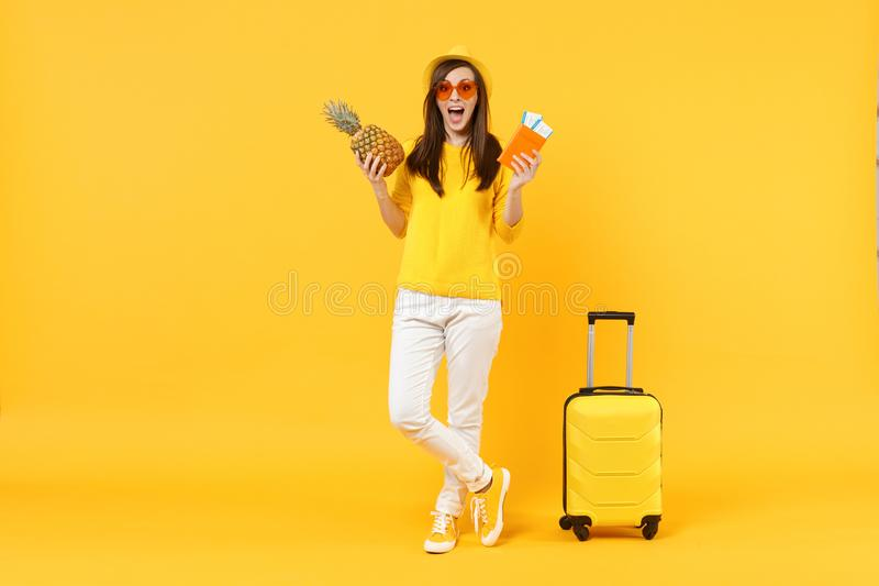 Excited traveler tourist woman in hat holding passport tickets, fresh pineapple fruit isolated on yellow orange. Background. Passenger traveling abroad on stock photography