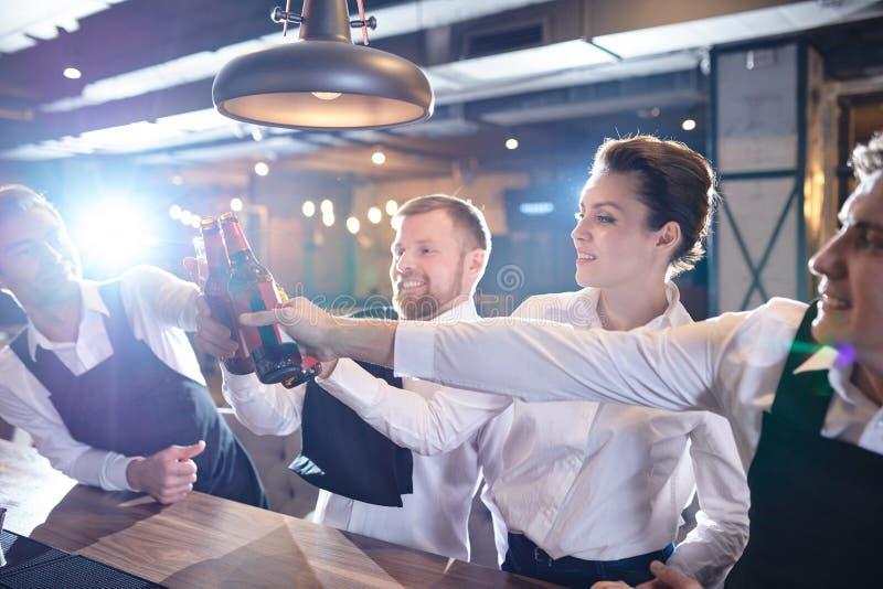Excited väntande personal som dricker för lyckad arbetsförskjutning royaltyfri fotografi