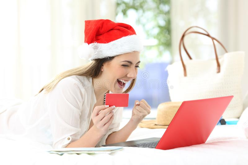 Excited woman buying online on christmas holidays. Lying on a bed in an hotel room royalty free stock photos