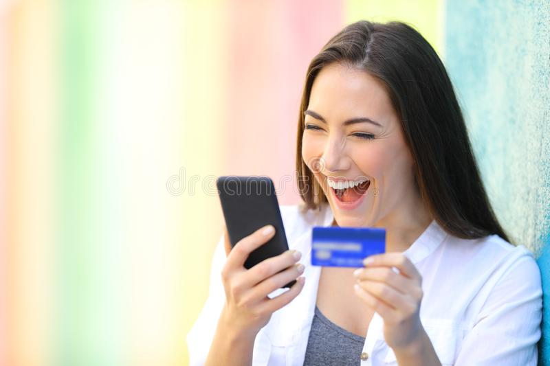 Excited woman buying online finding amazing offers. On smart phone in a colorful street royalty free stock images