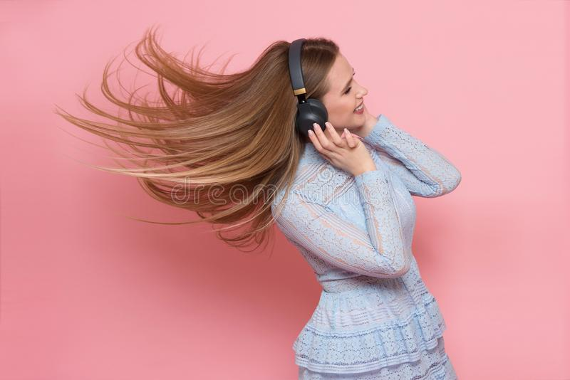 Excited woman dancing and listen to music wearing headphones in pink wall royalty free stock image