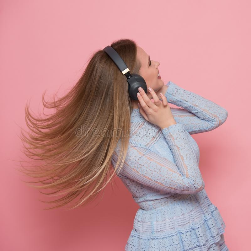 Excited woman dancing and listen to music wearing headphones in pink wall stock photos