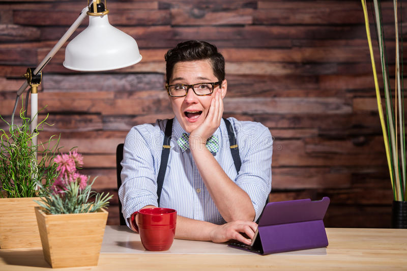 Excited Woman at Desk. Happy dapper woman wearing glasses and bowtie with cup and tablet computer royalty free stock image