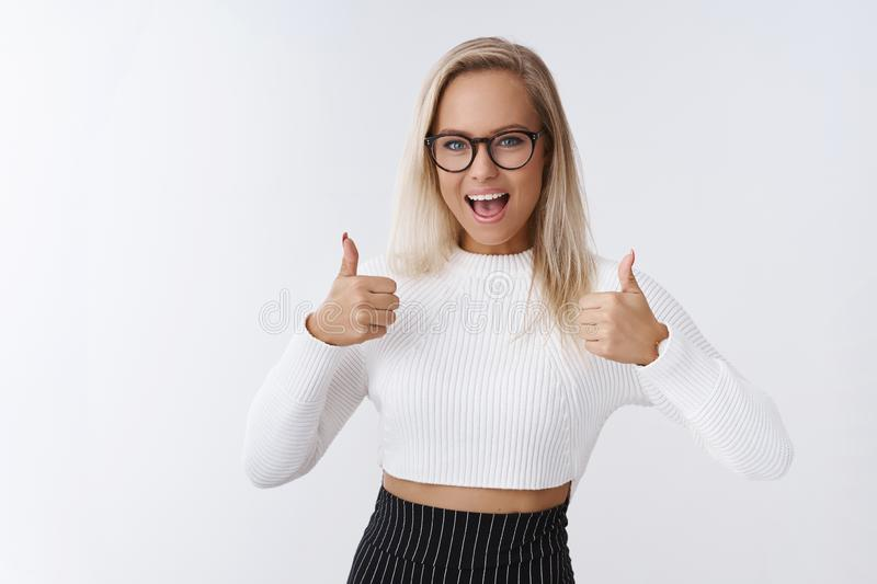 Excited woman giving green light and approval to friend suggesting go for it, showing thumbs up amused and impressed. Liking awesome outfit encouraging mate royalty free stock image