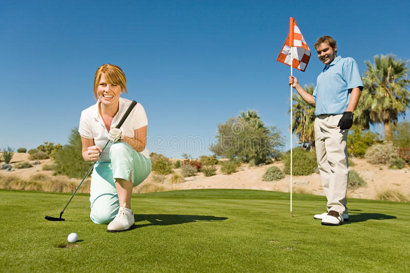 Excited Woman On Golf Club. Excited women playing golf with men holding flag in background royalty free stock photography
