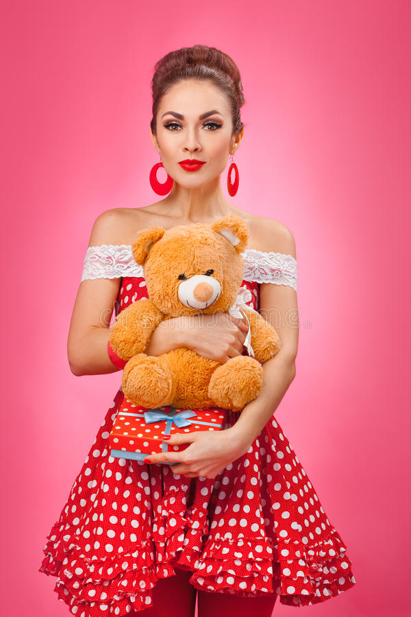 Excited Woman Holding Gift Box and Teddy Bear. Funny portrait of a smiling cute young female model embraces gift box and toy bear. Pink Background royalty free stock image