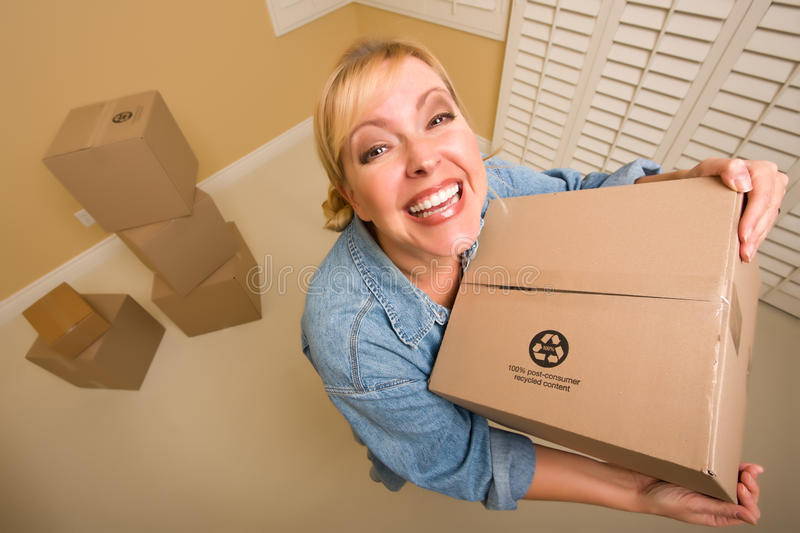Excited Woman Holding Moving Boxes in Empty Room stock image