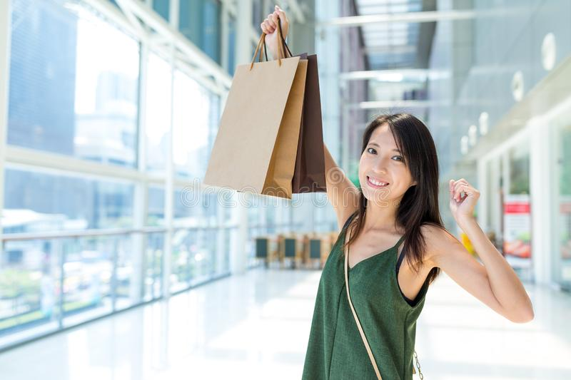 Excited woman holding up shopping bag in the mall stock photo