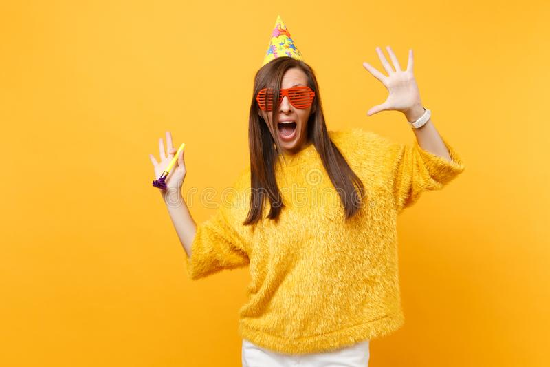 Excited woman in orange funny glasses birthday hat with playing pipe spreading hands, celebrating, enjoying holiday. Isolated on yellow background. People royalty free stock image