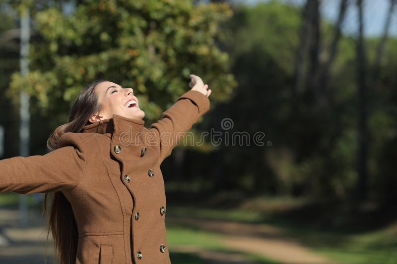 Excited woman outstretching arms in a park in winter stock images