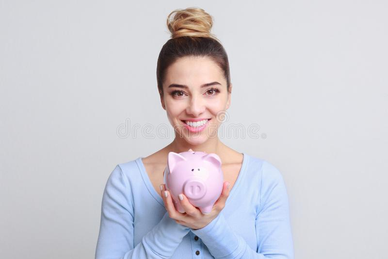 Excited woman with piggy bank on background. Excited woman with piggy bank, looking at camera, grey studio background stock images