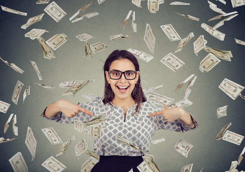 Excited woman pointing fingers at herself in disbelief of being a winner under a money rain stock photo