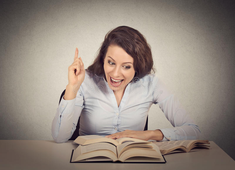 Excited woman reading book has idea stock photography