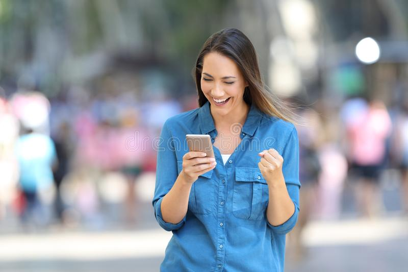 Excited woman reading good news online on the street. Front view of a excited woman reading good news in a smart phone online on the street stock photography