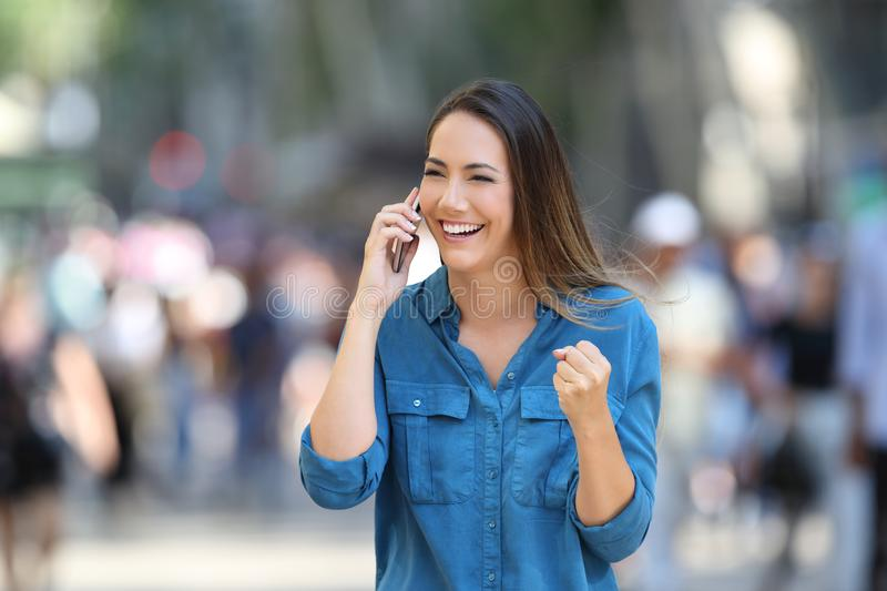 Excited woman receiving good news on phone. In the street stock photo