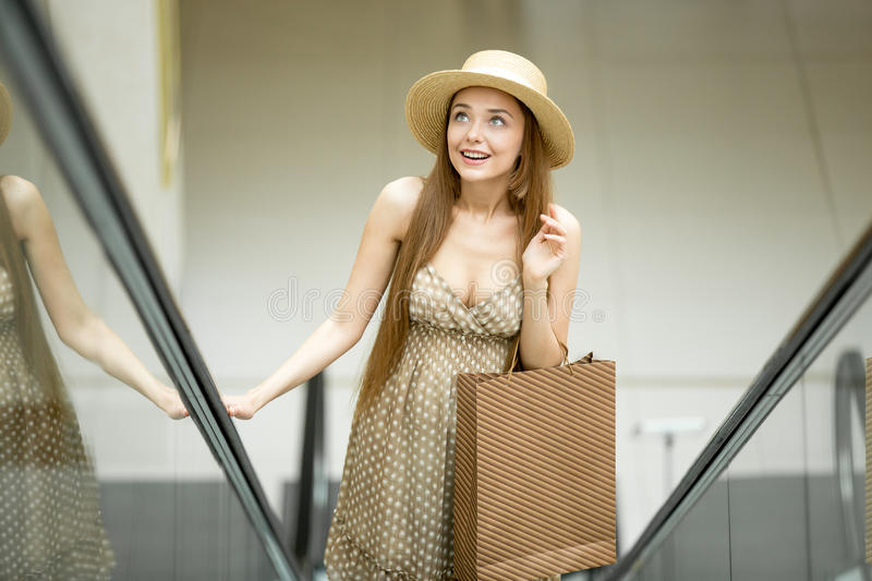 Excited woman in shopping centre standing on escalator. Young beautiful woman wearing a hat and cute polka dot dress carrying shopping bag standing on escalator royalty free stock photography