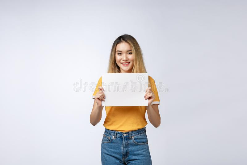 Excited woman showing empty blank paper card sign with copy space for text. Gorgeous multi ethnic Chinese Asian and. White Caucasian female model isolated on royalty free stock images