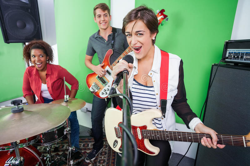 Excited Woman Singing While Band Playing Musical. Portrait of excited women singing while band playing musical instrument in recording studio royalty free stock photos