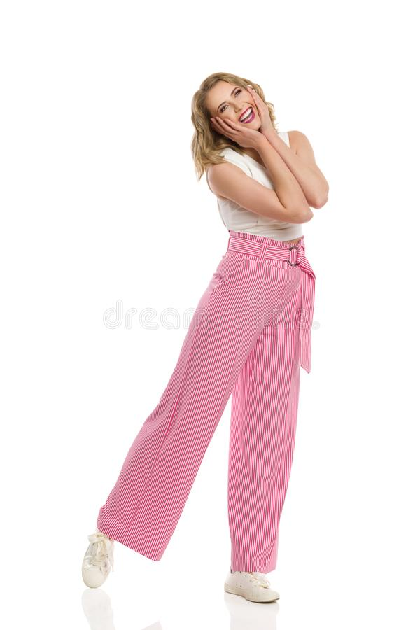Excited Woman In Striped Wide Legs Trousers Is Holding Head In Hands. Excited young woman in striped wide legs trousers is holding head in hands, laughing and royalty free stock image